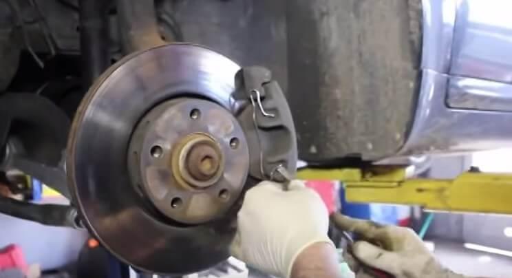 Демонтируем металлическую скобу на суппорте Ауди А6 С5